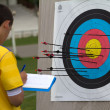 Stock Photo: Unidentified competitor is checking his archery accuracy .