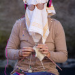 Stock Photo: Old womknitting with dish towel on face.