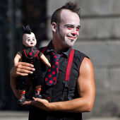 Clown holding a doll in the street. — Stock Photo
