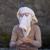 Old street performer with a dish towel on the face. — Stock Photo