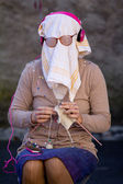 Old woman knitting with a dish towel on the face. — Stock Photo