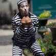 Stock Photo: Handcuffed clown in street.
