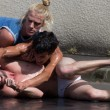 Two semi-naked dancers are fighting on the ground. — Stock Photo