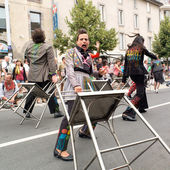 Street performer carrying bar stools. — Stock Photo