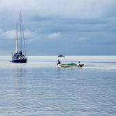 A small white fishing boat with green nets. — Stock Photo