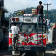 Stock Photo: Two men are standing on two ladders outside of old colored bus.
