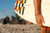 Closeup of a surfer holding a surfboard — Stockfoto