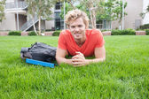 College student lying in the grass — Stock Photo