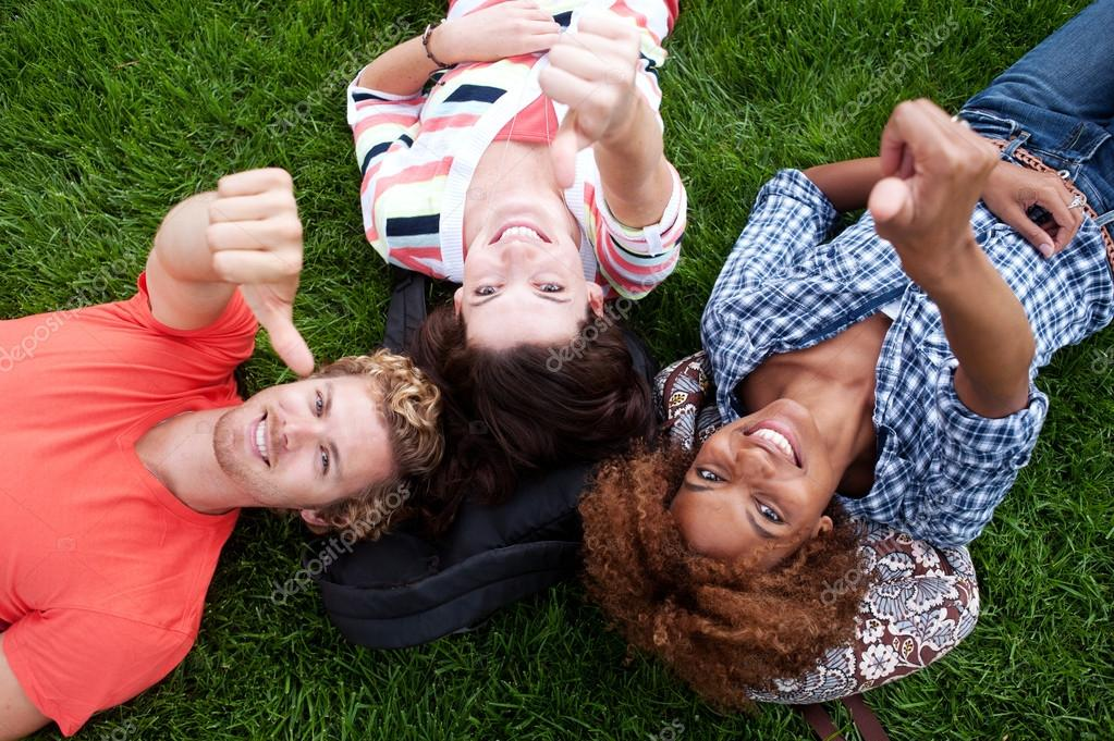 Group of happy college students lying in the grass looking up — Stock Photo #13486139