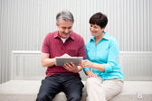 Mature couple with tablet — Stock Photo