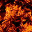 Burning embers in the dark - Stock Photo