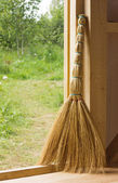 Besom in doorway of wooden country house — Stock Photo