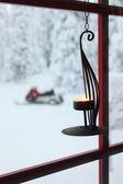 Decoratieve kaars op venster en sneeuwscooter — Stockfoto