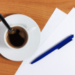 Cup of coffee on table with papers and pen — Stock Photo