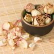 Dried rosebuds in teacup and petals diagonal view — Stock Photo #14100916