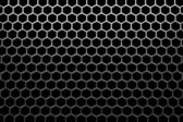 Steel grid with hexagonal holes under top straight light — Stock Photo