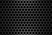 Steel grid with hexagonal holes under straight central light — Stock Photo