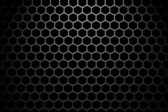 Steel grid with hexagonal holes under wide spot light — Stock Photo