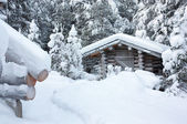 Small wooden blockhouse under white snow — Stock Photo