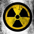 Stock Photo: Nuclear radiation symbol painted on board with grungy dirty stains all over it