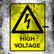 High voltage sign drawn at board with grungy dirty stains all over it - Stock Photo