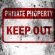 Keep out sign painted on board with grungy dirty stains all over it - Stock Photo