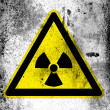 Nuclear radiation sign drawn on board with grungy dirty stains all over it — Stock Photo #14962221