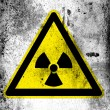 Nuclear radiation sign drawn on board with grungy dirty stains all over it — Stok fotoğraf
