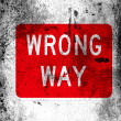 Wrong way road sign painted on board with grungy dirty stains all over it — Stock Photo