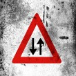 Two-way traffic straight ahead road sign painted on board with grungy dirty stains all over it — Stock Photo #14963563