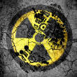 Nuclear radiation symbol painted on cracked ground with vignette with dirty oil footprint over it — Stock Photo