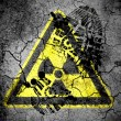 Nuclear radiation sign drawn on cracked ground with vignette with dirty oil footprint over it — Stock Photo #14964821