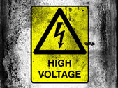 High voltage sign drawn at board with grungy dirty stains all over it — Stock Photo