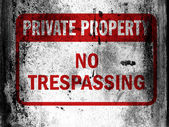 No trespassing sign painted on board with grungy dirty stains all over it — Stock Photo