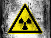 Nuclear radiation sign drawn on board with grungy dirty stains all over it — Stock Photo
