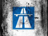 Autobahn road sign painted on board with grungy dirty stains all over it — Stock Photo
