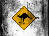 Kangaroo road sign painted on board with grungy dirty stains all over it — Stock Photo