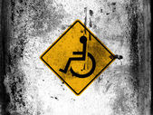 Disabled road sign painted on board with grungy dirty stains all over it — Stock Photo