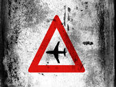 Low flying aircraft or sudden aircraft noise road sign painted on board with grungy dirty stains all over it — Stock Photo