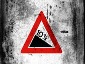 Steep hill downwards road sign painted on board with grungy dirty stains all over it — Stock Photo