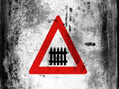 Level crossing with barrier or gate ahead road sign painted on board with grungy dirty stains all over it — Stock Photo
