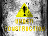 Under construction caption painted on board with grungy dirty stains on it — Stock Photo