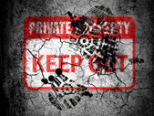 Keep out sign painted on cracked ground with vignette with dirty oil footprint over it — Stock Photo