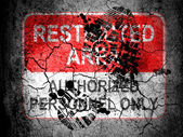 Restricted area sign painted on cracked ground with vignette with dirty oil footprint over it — Stock Photo