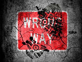 Wrong way road sign painted on cracked ground with vignette with dirty oil footprint over it — Stock Photo