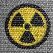 Nuclear radiation symbol painted on grey fabric — Stock Photo #14971725