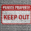 Keep out sign painted on grey fabric - Stock Photo