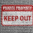 Stock Photo: Keep out sign painted on grey fabric