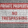 Stock Photo: No trespassing sign painted on grey fabric