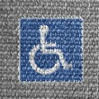 Disabled road sign painted on grey fabric — Stock Photo